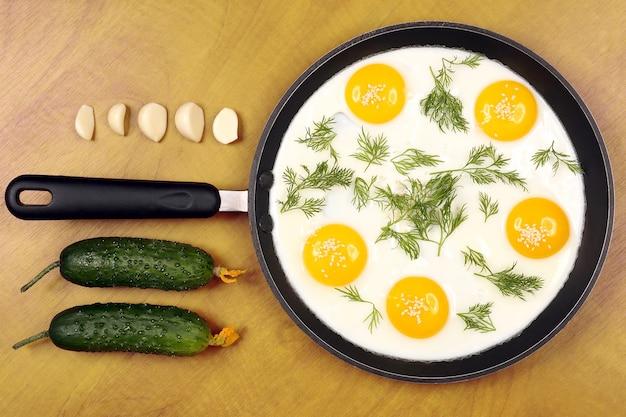 A panela sobre a mesa com ovos mexidos fritos com endro e pepino, alho. pequeno-almoço saudável e saudável