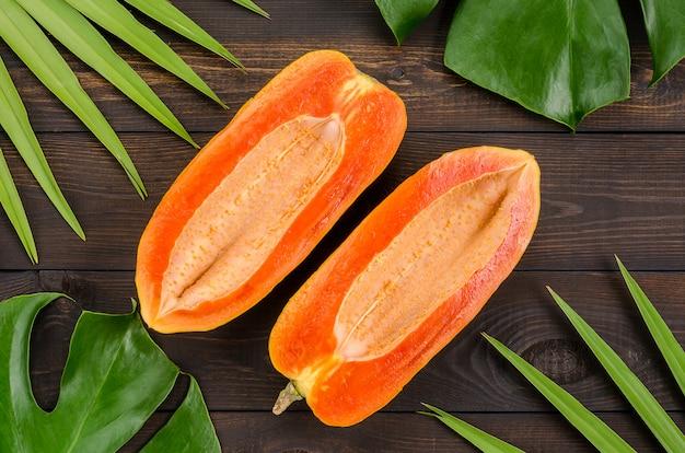 A papaia cortou ao meio em um fundo de madeira escuro.