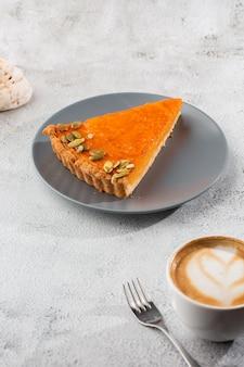 A parcela de torta aberta da abóbora alaranjada brilhante deliciosa na placa cinzenta, decorada com as sementes de abóbora com sobremesa bifurca-se close-up, vista superior. fundo de mármore brilhante. copie o espaço. vertical. menu para café