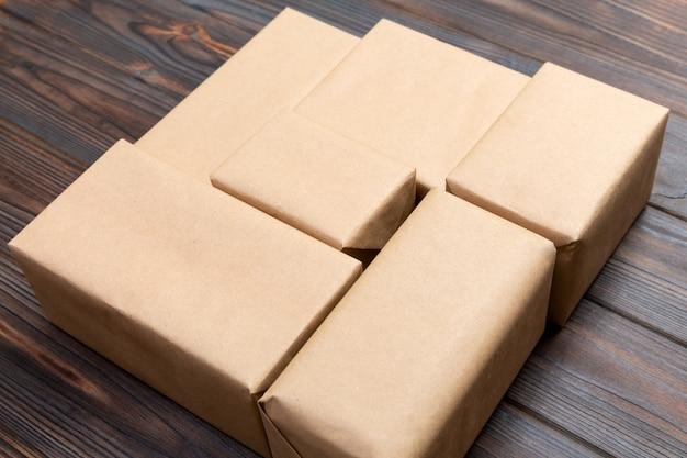 A parcela do pacote do pacote do correio de brown para você projeta. caixa de papelão sobre um fundo escuro de madeira