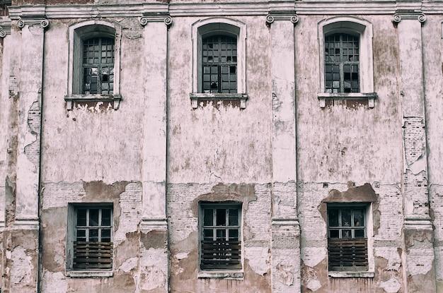 A parede abandonada velha e danificada com janelas com vidro quebrado