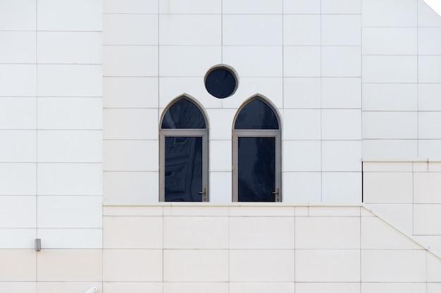 A parede branca com janelas arqueadas, detalhe de exterior da construção, geometria urbana, copia o espaço. fundo de arquitetura abstrata estilo minimalista.