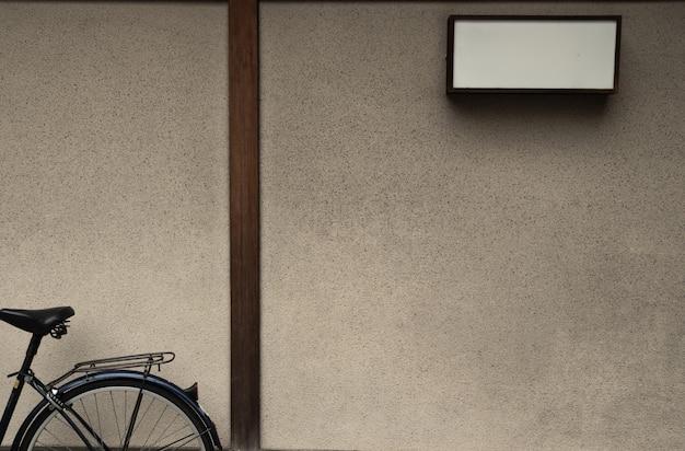 A parede da casa japonesa velha do chiqueiro com a caixa leve vazia e a bicicleta velha. backgound com espaço de cópia pronto.