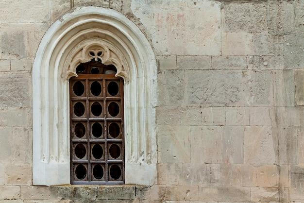 A parede de pedra com um antigo portão de ferro na cor escura. a principal entrada da fortaleza khotyn.