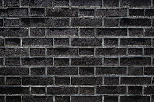 A parede de tijolo preto escuro tem uma superfície áspera como imagem de fundo.