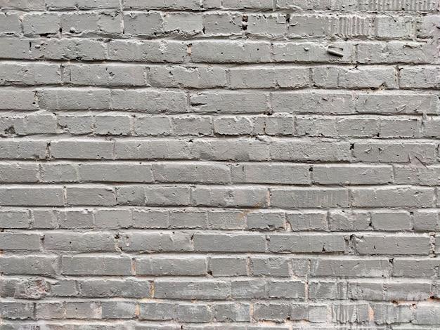 A parede de tijolos é branca e cinza.
