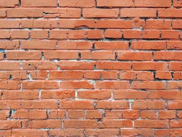 A parede de tijolos é de cor laranja vermelha.