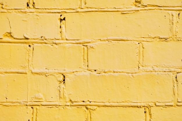 A parede de tijolos é pintada de amarelo. fundo.