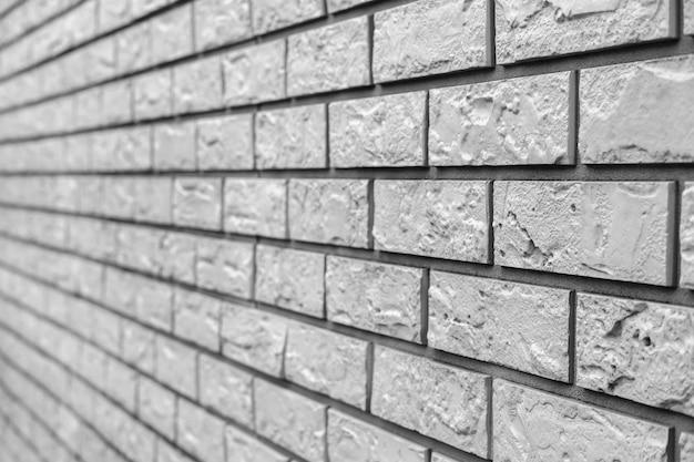 A parede de uma casa de campo, forrada com painéis de fachada de plástico branco em forma de tijolos.