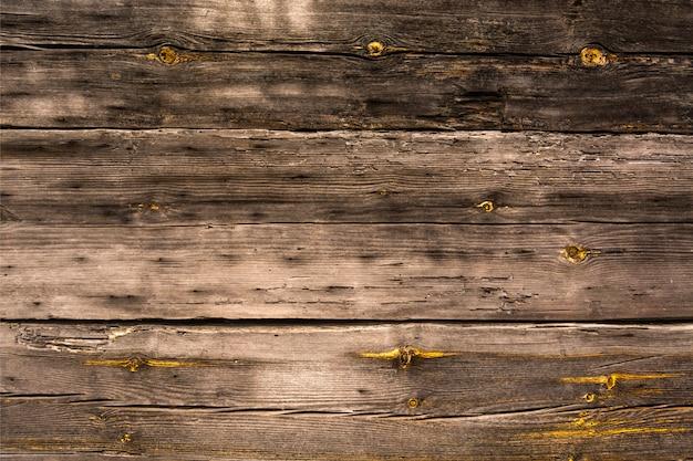A parede de uma casa de madeira. placas antigas sem pintura. a textura das placas
