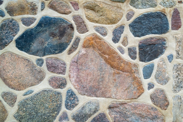 A parede é feita de pedra natural e cimento. fragmento de uma parede de pedra texturizada e colorida. brilhante