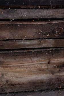 A parede é feita de placas velhas sujas, o fundo é feito de madeira marrom escura coberta com poeira e teias de aranha ...