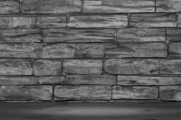A parede é feita de tijolos de cor preto e branco e tábuas de madeira com um ponto de iluminação.