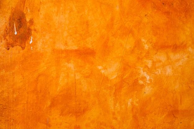 A parede textured escovou o fundo pintado, cor de óleo alaranjada abstrata.