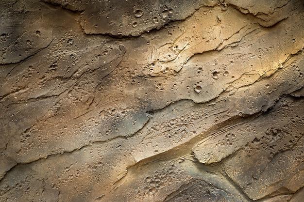 A parede velha do cimento é áspera para o fundo.