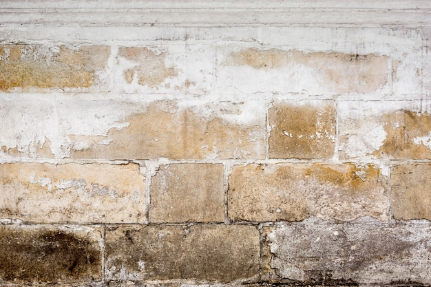 A parede velha dos blocos com rachaduras e microplaquetas. fundo.