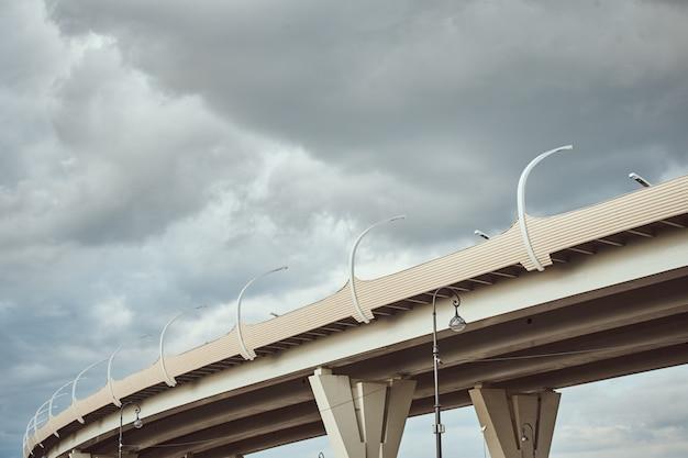 A parte da ponte moderna com rua conduziu luzes contra o céu nebuloso. closeup de construção de engenharia