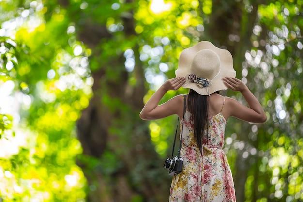 A parte de trás da garota felicidade usando um chapéu de palha no jardim