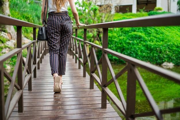 A parte de trás da mulher andando na ponte de madeira