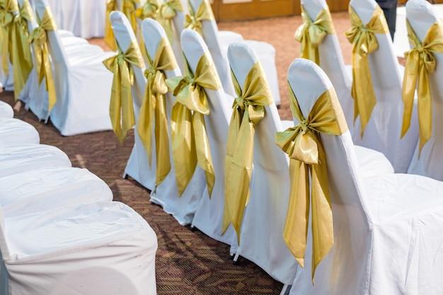 A parte de trás das cadeiras de casamento amarelas e douradas