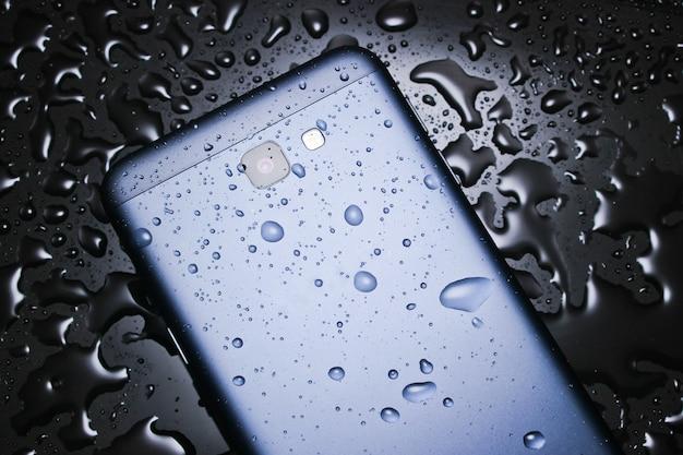 A parte de trás do smartphone com água cai na mesa preta