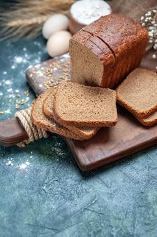 A parte superior do pão preto dietético com trigos na placa de madeira espinhos com farinha de ovos de flores em uma tigela sobre fundo azul