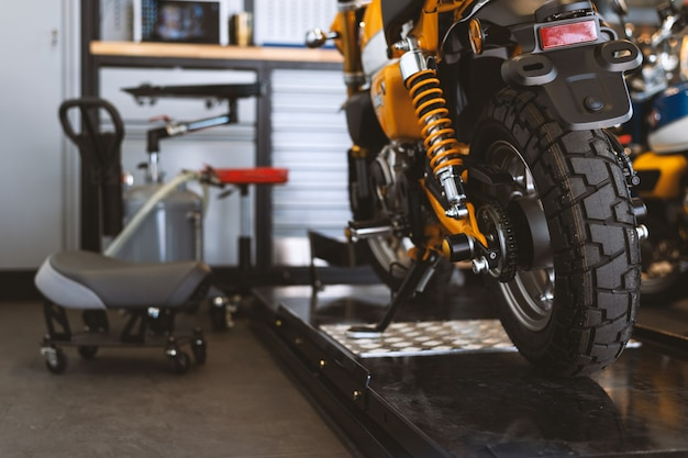 A parte traseira das motocicletas clássicas em pé na oficina