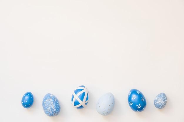 A páscoa azul decorou os ovos isolados na superfície branca.