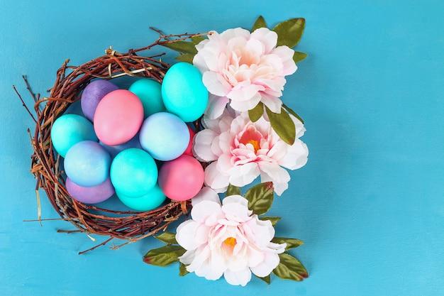 A páscoa coloriu os ovos coloridos que encontram-se dentro do ninho ao lado das flores em um fundo azul.