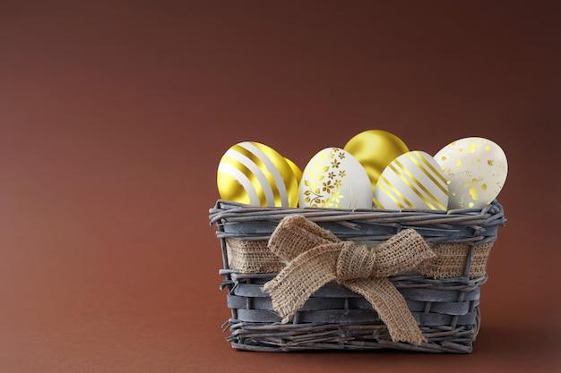 A páscoa feliz, tingiu ovos coloridos na cesta no fundo de uma cor.