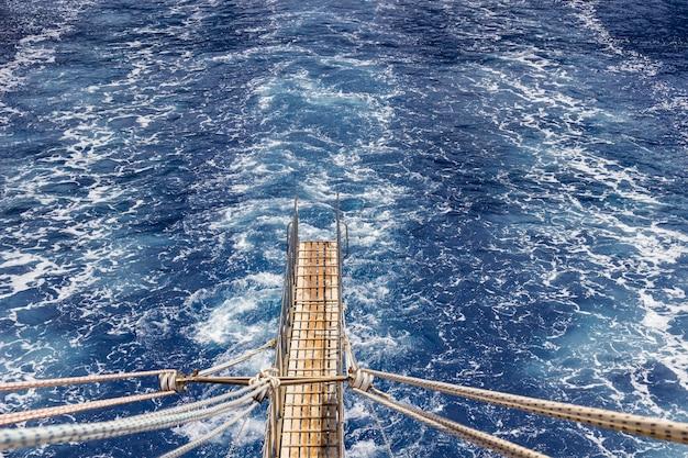 A passarela e a trilha na água do navio que parte para o mar