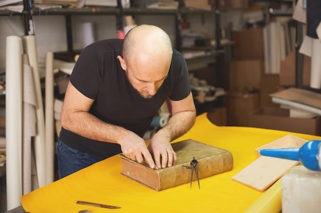 A pasta de livros restaura um livro antigo na oficina de artesanato