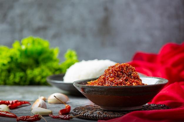 A pasta de porco friável misturou com os ingredientes decorativos bonitos, comida tailandesa.