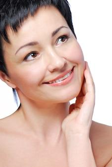 A pele bonita e saudável do rosto de uma mulher feliz e sorridente adulto médio