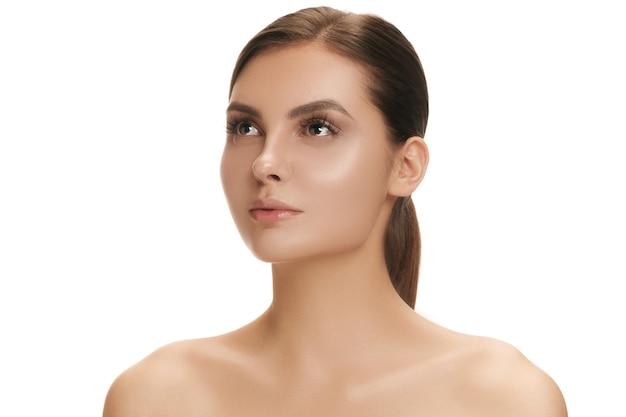 A pele perfeita e limpa do rosto de uma mulher na parede branca