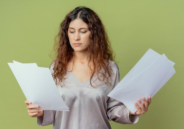 A pensar jovem e bonita funcionária de escritório segurando e olhando papéis isolados em verde oliva