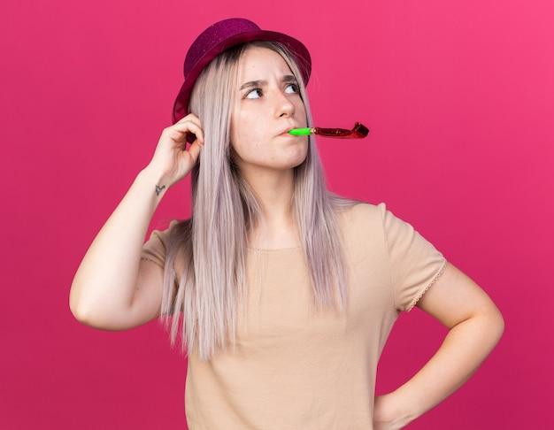A pensar uma jovem linda com um chapéu de festa a soprar um apito de festa a coçar a cabeça