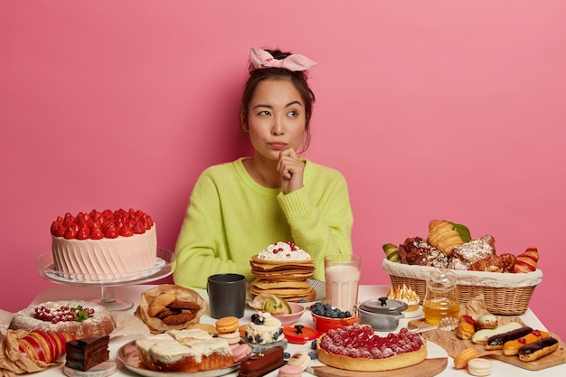 A pensativa senhora coreana gosta de lanches saborosos, come doces saborosos, bolos e panquecas, pensa em como perder o vício em doces, segura o queixo, posa em uma mesa festiva com confeitaria artesanal.