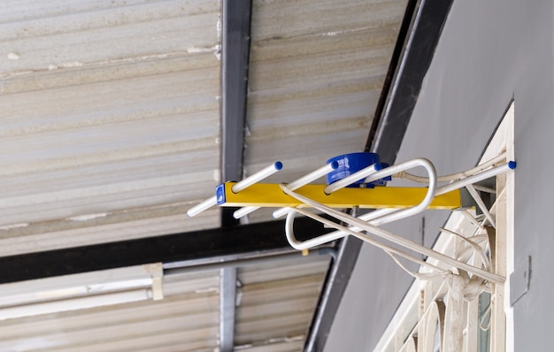 A pequena antena da televisão digital está pendurada perto da janela com corda de plástico sob o beiral para uma boa posição para receber o sinal, vista frontal para o espaço da cópia.