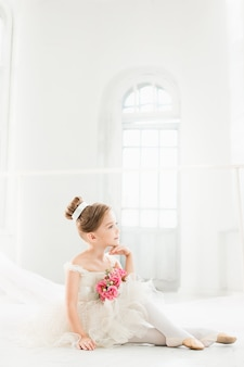 A pequena bailarina com tutu branco na sala de aula de ballet