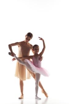 A pequena bailarina dançando com o professor pessoal de balé no estúdio de dança