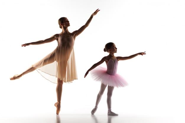 A pequena bailarina dançando com professor de balé pessoal no estúdio de dança