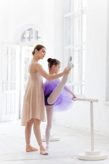 A pequena bailarina posando no bar de ballet com o professor pessoal no estúdio de dança
