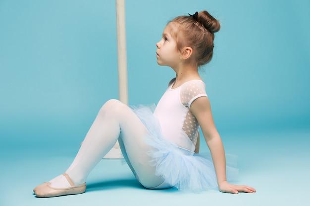 A pequena dançarina balerina sobre fundo azul