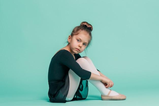 A pequena dançarina de balerina na parede azul