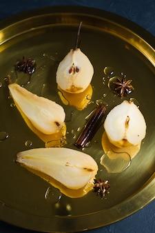 A pera cortada escalfou em uma bandeja do ouro, cozinhada no vinho branco.