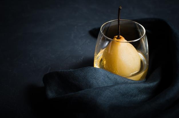 A pera escalfou em um vidro, cozinhado no vinho branco.