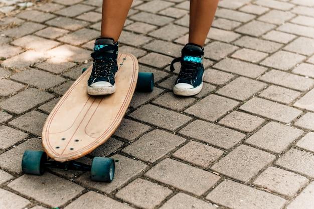 A perna da menina nas sapatilhas que estão em um skate.
