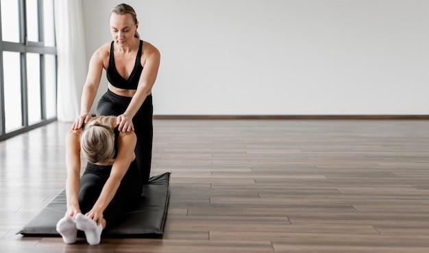 A personal trainer feminina e seu cliente copiam espaço