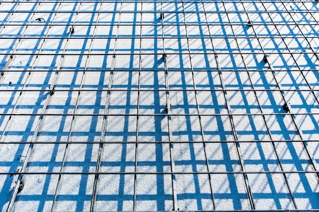 A perspectiva de malha de metal reforçada em um canteiro de obras no inverno